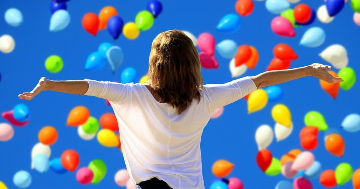 カラフルな風船の前で両手を広げる女性